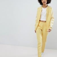 adidas Originals adicolor Three Stripe Track Pants In Yellow at asos.com