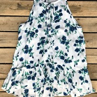 Floral and Summer just go together! Our Keep Me Guessing Top is a sleeveless top with soft floral print throughout. V-neckline with tie closure and buttons down the front. Ruffles accent the bottom high/low hem. Made to be flowy.