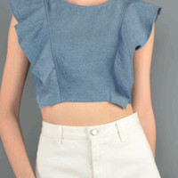 Show off some skin with a feminine flair in the Water Fall Ruffle of Flounce Light Denim Crop Top. Featuring a round neckline, sleeveless top with water fall ruffled design, crop style top with hidden size zipper closure. Pair with high waist maxi skirt or