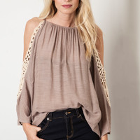 This airy gauze blend fabrication top features a round neckline, crochet cold shoulder with quarter-length sleeves, adjustable spaghetti shoulder straps, relax cut fit. Pair with denim cut off. Unlined.