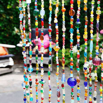 Glass beaded curtain with strands of multi colored glass beads. Bring sparkles of colored light into your home!
