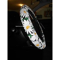 Steering wheel cover with large white daisies on black background with green leaves.  Floral car accessories.