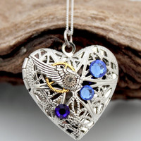 Steampunk locket silver plated filigree heart with blue Swarovski crystals, wing and vintage watch parts- Unique jewelry