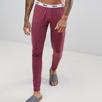 ASOS DESIGN meggings in burgundy with branded waistband at asos.com