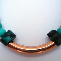 Unisex elasticated bracelet with magnesite beads with a copper hollow bar in the center and turquoise heisha beads on either side.