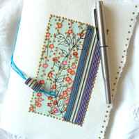 Pretty turquoise and blue design covers this Sketch Book, Journal or Notebook with blank pages