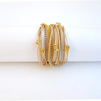 Two-in-one - Wrapped bracelet or necklace. Off white round leather & gold plated chains and beads
