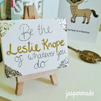 """Mini canvas and artist easel with inspiring Parks and Recreation quote, """"Be the Leslie Knope of whatever you do"""" with silver glitter"""