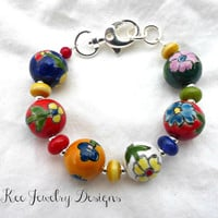 Flower painted ceramic beads with lamp work glass bracelet.