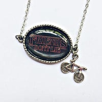 Friends Don't Lie Necklace: resin cabochon pendant and bicycle charm in silver