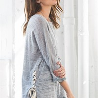 Burnout-like pullover sweater in an effortless, slightly loose fitting, slightly sheer, square neckline, features fringe trim and side slit with grommet and lace up detailing. 3/4 sleeves with fringe trim.