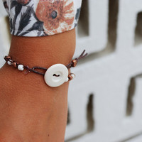 Crocheted bracelet with glass white and brown beads clasped together with a big white vintage button and tassel with matching beads