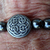 Men's elastic bracelet with grey hematite beads and a round pewter Celtic bead as the center focal point.