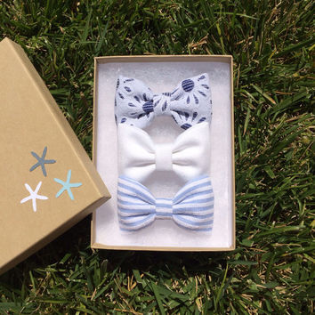 Blue and white eyelet, white denim, and baby blue striped hair bows from Seaside Sparrow.  Seaside Sparrow bows make the perfect gift.