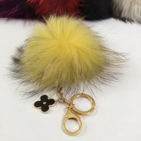 Fur pom pom keychain, bag pendant with flower charm in yellow with black markings color tone