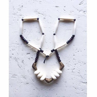 Long beaded necklace with cream bone beads, brass beads from Ghana and dark purple Native American glass crow beads An Astrid Endeavor