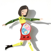 Articulated pregnant paperdoll with green and red dress. It's a girl and a boy.