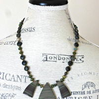 Green gemstone, metal and stone necklace.